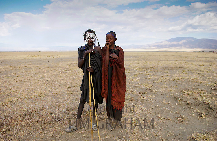 Young recently circumcised Masai Warriors (moran) with traditional face paint after 'coming of age' and a young Masai girl in the Serengei Plains, Tanzania.