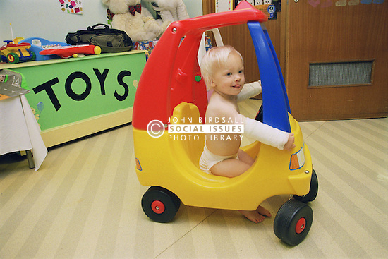 Young boy with bandaged arms playing in hospital playroom,