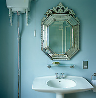 An antique Venetian mirror hangs above the wash basin in the small bathroom