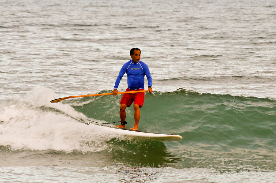 Older Hawaiian man Stand-up paddle board surfing, Kauai, Hawaii