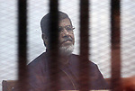 FILE PHOTO: Egyptian ousted president Mohammed Morsi sits behind the defendants cage as he attends his trial at the police academy on the outskirts of the capital Cairo, on February 26, 2017. Former President Mohamed Morsi died on Monday in court after the conclusion of a trial session in the espionage lawsuit, Egyptian state TV said. Photo by Stranger