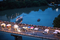 Tent vendors line up and down the Congress Avenue Bridge as Bat watchers gather to watch Austin's 1.5 million Mexican free-tailed bats take flight over Lady Bird Lake during the Annual Austin Bat Festival in downtown Austin, Texas - Stock Image.