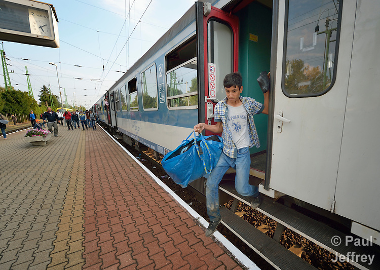 A refugee boy climbs down from a train as it arrives in the Hungarian town of Hegyeshalom. Migrants and refugees aboard the train walk from here across the border into Austria. Hundreds of thousands of refugees and migrants flowed through Hungary in 2015, on their way to western Europe from Syria, Iraq and other countries.