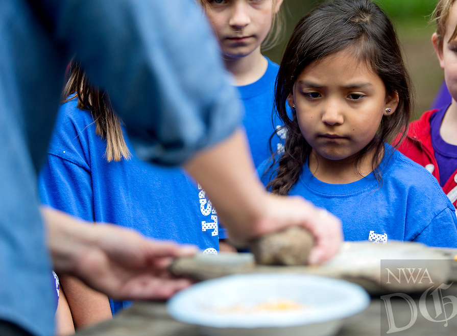 NWA Democrat-Gazette/JASON IVESTER<br /> Janice Santillian (cq), Elm Tree Elementary first-grader, watches closles as Carly Squyres (cq), education assistant, grinds corn on Thursday, May 19, 2016, outside the barn at the Shiloh Museum of Ozark History in Springdale. The five first-grade classes from the Bentonville school visited the museum as they begin their studies on Arkansas history.