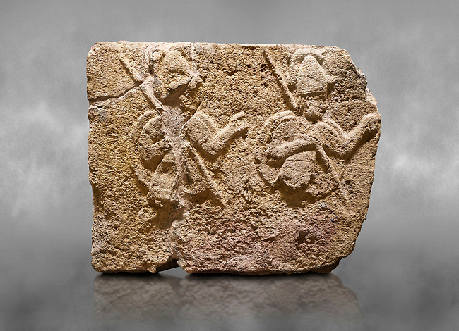 Hittite relief sculpted orthostat stone panel of Long Wall Limestone, Karkamıs, (Kargamıs), Carchemish (Karkemish), 900-700 B.C. . Anatolian Civilisations Museum, Ankara, Turkey. Two helmeted soldiers in short skirt carry shield on their backs and spear in their hands.<br /> <br /> On a grey art background.