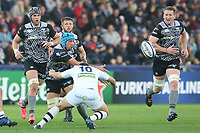 Justin Tipuric of Ospreys offloads the ball under pressure from Camille Lopez of Clermont during the Champions Cup Round 1 match between Ospreys and Clermont at The Liberty Stadium, Swansea, Wales, UK. Sunday 15 October 2017