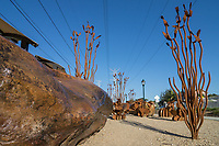 A sculpture garden made out of rusted metal parts in a desert theme: ocotillos, barrel cacti, opuntia, and rust-colored rocks.