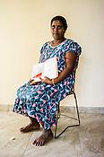 A Sri Lankan woman poses for a photo with the CHDR- Child Health Development Record Card (immunization/vaccination card) in the Ministry of Health office in Tharmapuram Village in Kilonochchi, Sri Lanka.  Photo: Sanjit Das/Panos