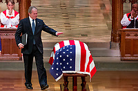 Former President George W. Bush touches the flag-draped casket of his father, former President George H.W. Bush, after speaking during his State Funeral at the National Cathedral, Wednesday, Dec. 5, 2018, in Washington. (AP Photo/Andrew Harnik, Pool)