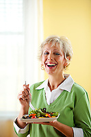 Series with a mature couple, mid 50's, in various themes, including healthy eating, medical and fun.  Isolated on white and an interior room. Having a green salad.