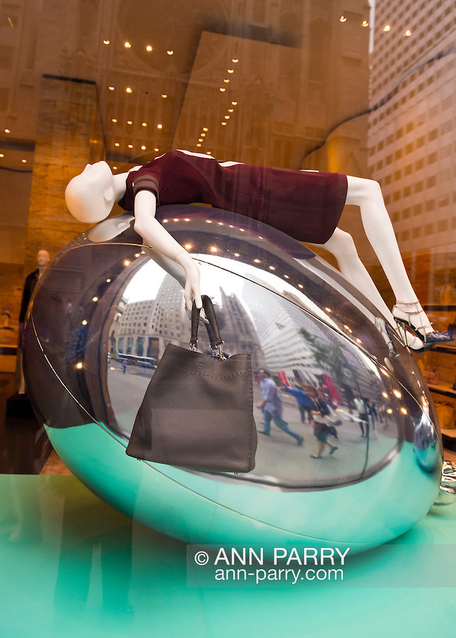 Manhattan, New York, U.S. - May 21, 2014 - In the Fendi 5th Avenue store window display, a manniquin wearing a brown dress and shoes is in supine position draped over a large structure resembling a silver Mylar balloon, during a pleasant Spring day in Manhattan. A brown leather Fendi purse hangs from one hand.