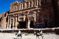 """Jordan. Petra. The archeological site is part of the UNESCO world heritage project.  The Nabataeans were an arabian industrious tribe which settled down in southern Jordan 2000 years ago. Petra is located at the bottom of a spectacular deep gorge surrounded by mountains. Tomb """"Sextius Florentius"""". Bedouin family on the dunkey on their way home. The woman wears a long dress and a veil on her head as part of muslim tradition and religion. © 2002 Didier Ruef"""
