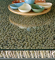 The glass of this table top is held in place by hundreds of tiny sculpted figures