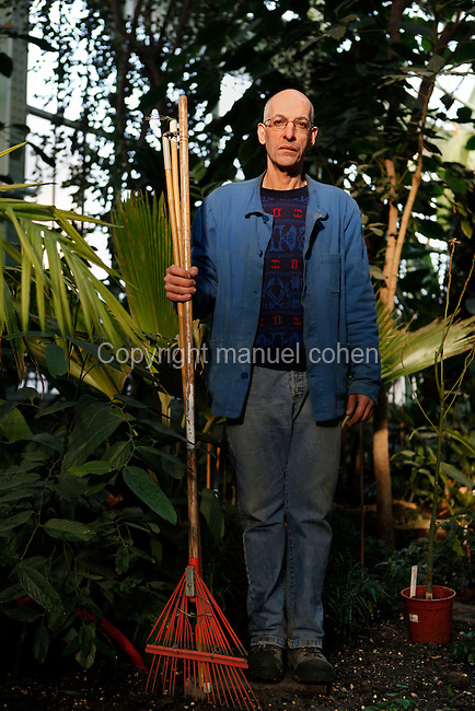 Tropical Rainforest Glasshouse (formerly Le Jardin d'Hiver or Winter Gardens), 1936, René Berger, Jardin des Plantes, Museum National d'Histoire Naturelle, Paris, France. Portrait of Karim Benyoub, the gardener, full length,  holding a rake, surrounded by the luxuriant tropical foliage inside the Art Deco style building.