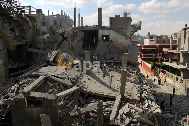 Palestinians look at the remains of house, which witnesses said was hit by an Israeli air strike in Khan Younis in the southern Gaza Strip August 9, 2014. Israel launched more than 20 aerial attacks in Gaza early on Saturday and militants fired several rockets at Israel in a second day of violence since a failure to extend an Egyptian-mediated truce that halted a monthlong war earlier this week. The Israeli military said that since midnight it had attacked more than 20 sites in the coastal enclave where Hamas Islamists are dominant, without specifying the targets. Medical officials in Gaza said two Palestinians were killed when their motorcycle was bombed and the bodies of three others were found beneath the rubble of one of three bombed mosques. The air strikes which lasted through the night also bombed three houses, and fighter planes also strafed open areas, medical officials said. Photo by Abed Rahim Khatib