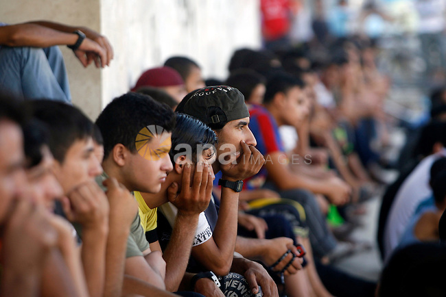 Palestinian youths watch a football match before breaking fast in southern Gaza strip town of Rafah, on 03 August 2012. Muslims fasting in the month of Ramadan must abstain from food, drink and sex from dawn until sunset. Photo by Eyad Al Baba