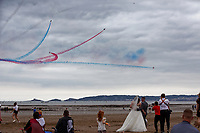 A married couple have their pictures taken while the Red Arrows perform during the Swansea Airshow 2019 over Swansea Bay, Wales, UK.