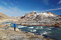 Hiker looking over glacial melt river and mountains, Sammileq Fjord, Ammassalik Island, East Greenland