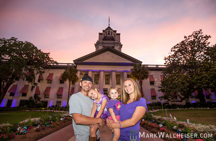 Seth Beckstead, left, and 4 year old Remi Pagean stand next to Pagean's mother Tony Beagles holding her 2 year old sister and cystic fibrosis carrier Shiloh Pagean during the Light Up CF event by the Cystic Fibrosis Lifestyle Foundation at the Florida Capitol in Tallahassee, Florida.