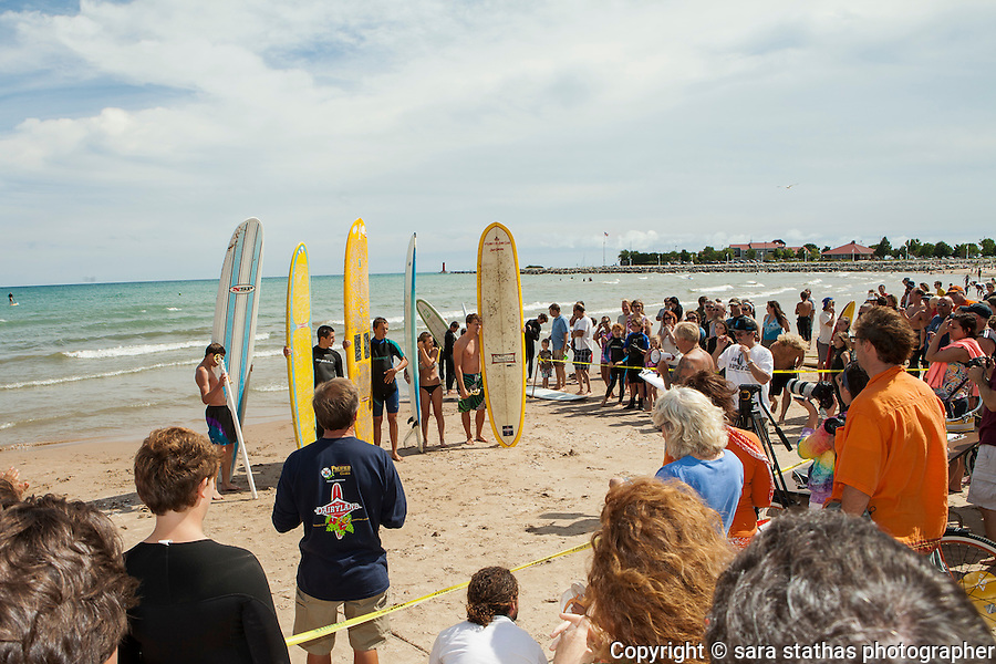 A crowd gathers around a group of competitors at the 25th annual Dairyland Surf Classic in Sheyboygan, Wisconsin on Lake Michigan.