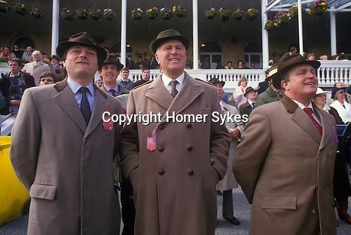 Men wearing tradition Cromie Coats ( L and R ) with velvet collars Aintree, horse race meeting. 1980s. UK