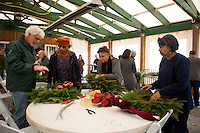 Friends of the Wissahickon Trail Ambassador Don Simon talks with participants (form left) Dorothy Page of Abington, Connie Sandlin of North Philadelphia, and Bobby Morris of Germantown about wreath decorating at the Winter in the Wissahickon event hosted by the Friends of the Wissahickon on December 1. (Dave Tavani/for NewsWorks)