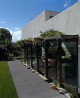 The wisteria-covered arbour is made from steel girders and runs the length of the living area