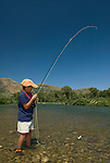 An eight-year-old boy brings a cutthroat trout to hand during a summer day on the South Fork of the Snake River, Idaho.