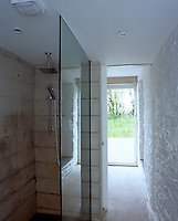 A concrete shower with a glass wall