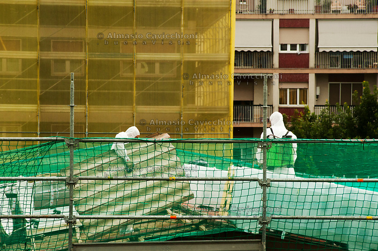 Milano, operai con tuta e maschere rimuovono lastre di amianto da un tetto.<br /> Milan, workers with overalls and masks remove asbestos sheets from a roof.