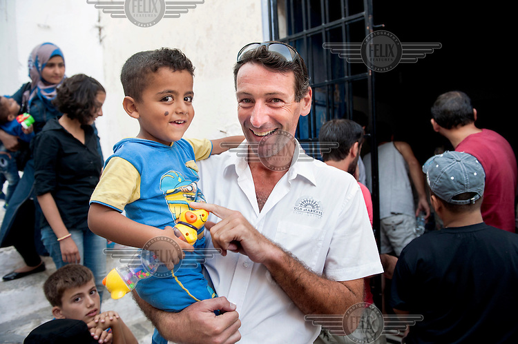 Hotelier Andrew Davies with a child at the refugee reception centre on Symi Island. Davies, a British ex-pat, helped found Solidarity Symi which helps refugees arriving from Turkey.