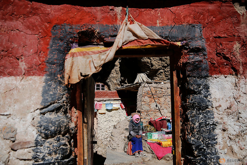A Tibetan woman sits in front of a house built in a rock at the shores of Namtso lake in the Tibet Autonomous Region, China November 18, 2015. Located four hours' drive from Lhasa at an altitude of around 4,718m (15,479 ft) above sea level, Namtso lake is not only the highest saltwater lake in the world but also considered sacred attracting throngs of devotees and pilgrims. REUTERS/Damir Sagolj