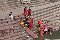 Pashupatinath Temple, Nepal.  Family Members Offer Prayers and Food Offerings for the Deceased on the Bank of the Bagmati River.  One woman places in the Bagmati a food offering in a floating dish made of sal leaves, the material preferred for such offerings.