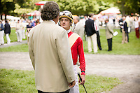 Jockey Julien Leparoux (R, foreground) talks to trainer Patrick Biancone (L, foreground) in the paddock before a race in Saratoga Springs, NY, United States, 5 August 2006.