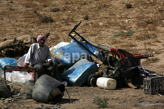 A Palestinian sits on the remains of his tent destroyed by the Israeli army, in the West Bank village of Faresiya near Tubas, Monday, July 19, 2010. Israeli forces demolished a cluster of tents and shacks belonging to Palestinians in the northern West Bank . Photo by Wagdi Eshtayah