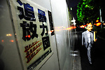 A businessman walks past a sign warning people to steer clear of mafia elements in Tokyo, Japan.