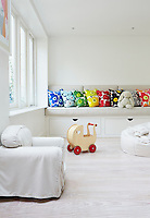 The nursery features space-saving storage beneath a banquette filled with bright Marimekko cushions
