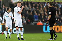 (L-R) Sam Clucas of Swansea City protests to referee Craig Pawson during the Premier League match between Swansea City and Crystal Palace at The Liberty Stadium, Swansea, Wales, UK. Saturday 23 December 2017