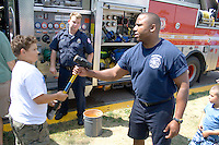 Firefighter demonstrating the use of the sledge hammer as a firefighting tool. Aquatennial Beach Bash Minneapolis Minnesota USA