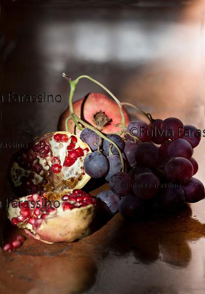 Frutti dell'autunno, melograno e uva nera