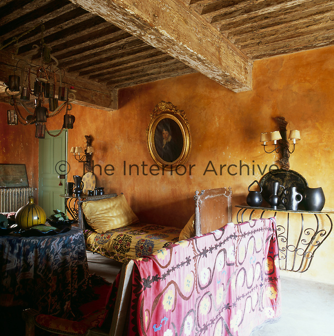A rustic sitting room with stone walls painted with natural pigments inspired by the colours of Provence, such as yellow ochre, while being careful to leave the original underlying layers. A period portrait painting hangs on the wall above an antique daybed, while pottery pieces are displayed on a wrought-iron table
