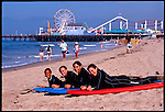 Four (4) young women learn to surf in Santa Monica, California near the Santa Monica Pier.