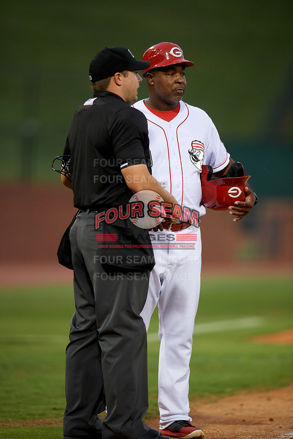 Greeneville Reds manager Gookie Dawkins (9) talks with home plate umpire Colin Baron during a game against the Pulaski Yankees on July 27, 2018 at Pioneer Park in Tusculum, Tennessee.  Greeneville defeated Pulaski 3-2.  (Mike Janes/Four Seam Images)