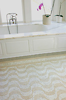 Aquarius, a custom natural stone mosaic, is shown in Botticino and Calacatta Tia hand chopped tumbled.