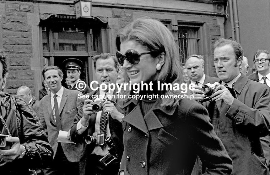 Jacqueline Kennedy Onassis, aka Jackie Kennedy, on a trip to Belfast, N Ireland, UK, with her husband, Aristotle Onassis, the Greek shipping magnate, who was visiting  local shipbuilders, Harland &amp; Wolff, on 5th September 1970.  The picture was taken in Queen Street, Belfast, where she and her husband were entertained to a buffet lunch in the Harland &amp; Wolff Social Club. The photo         includes Belfast Telegraph journalist, Barry White, Bob Renton, staff photographer, Daily Express, RUC  Detective Chief Inspector Cecil Patterson, behind  Jackie Onassis and in front of barred window, and Eddie Harvey, staff photographer, Belfast Newsletter. 197009050347a <br />