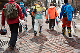 USA, Colorado, Aspen, skiers and snowboarders walk through the square towards the base of Aspen Mountain, Aspen Ski Resort
