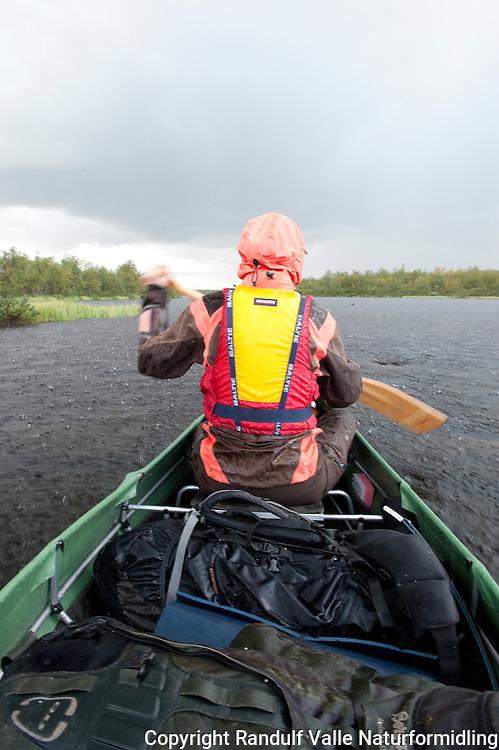 Kanopadler i fossregn. ---- Canoeist in heavy rain.