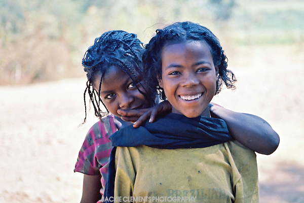 These two girls were selling papaya on the side of the road. They agreed to have their photo taken, and posed like stiff soldiers. I mimicked them and we all had a good laugh at each other. The next image taken shows their true nature.