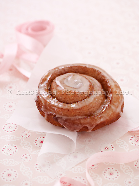 An iced cinnamon roll doughnut (Pershing) on a tissue square.