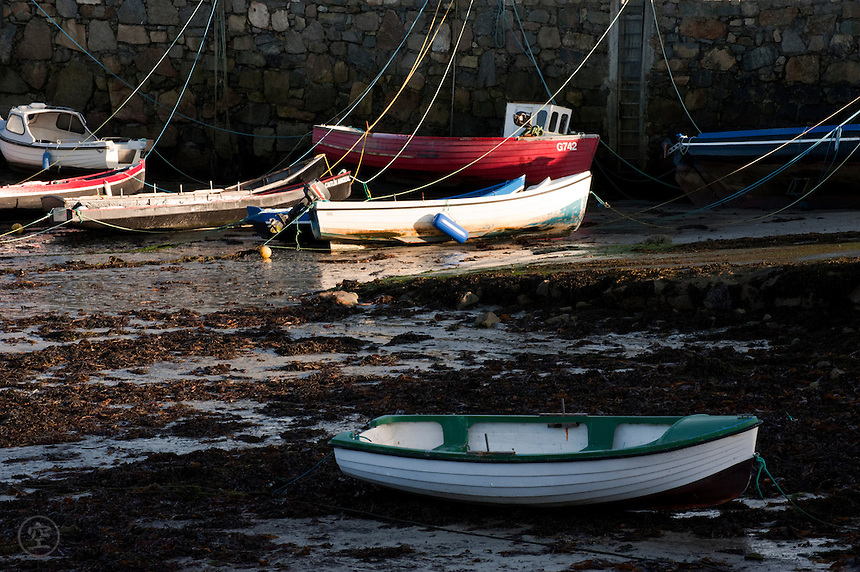 Fishing boats at low tide in the scenic Spiddal Harbour near Galway, Ireland.